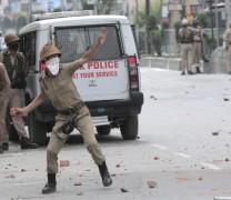 Cop pelting stones at protesting students.pic; Mudasir Khan